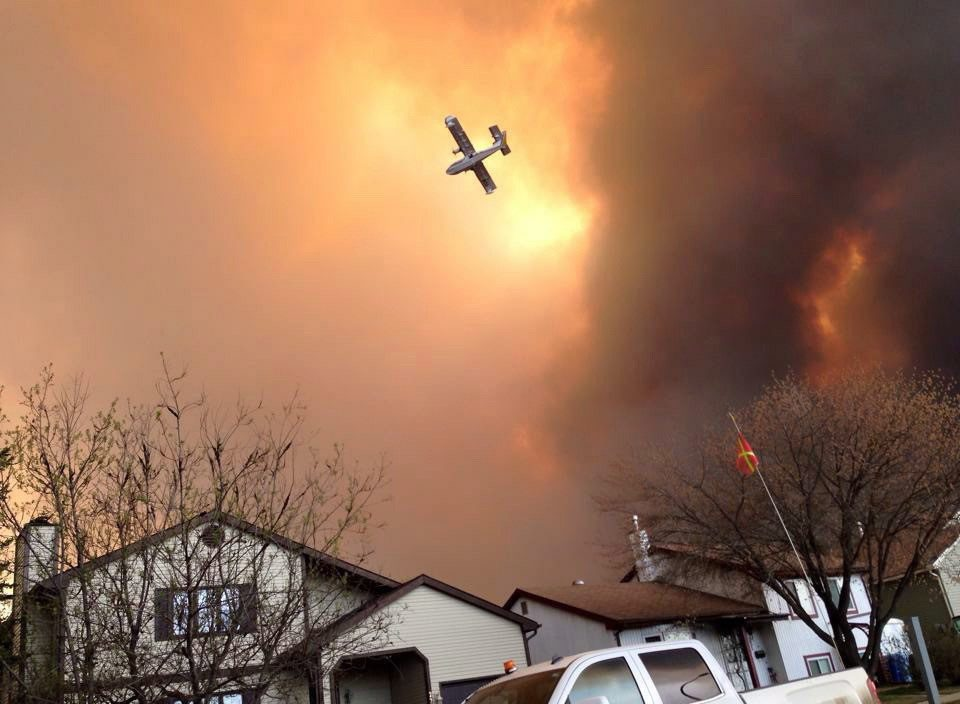 Smoke fills the air as a small plane flies overhead in Fort McMurray, Alberta on Tuesday May 3, 2016. Raging forest fires whipped up by shifting winds sliced through the middle of the remote oilsands hub city of Fort McMurray Tuesday, sending tens of thousands fleeing in both directions and prompting the evacuation of the entire city. THE CANADIAN PRESS/Kitty Cochrane