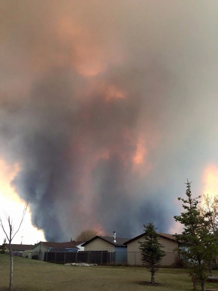 Fire burns and smoke fills the air near homes in Fort McMurray, Alberta on Tuesday May 3, 2016. Raging forest fires whipped up by shifting winds sliced through the middle of the remote oilsands hub city of Fort McMurray Tuesday, sending tens of thousands fleeing in both directions and prompting the evacuation of the entire city. THE CANADIAN PRESS/Kitty Cochrane